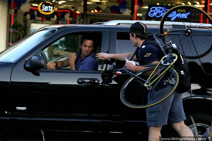 Vlad hands a motorist a flier